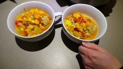 Two steaming bowls of vegetable and meatball soup